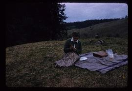 Unidentified woman sitting on blanket during journey to Alkali Lake, BC
