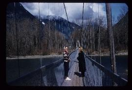 Two women standing on bridge over the Bella Coola River, BC