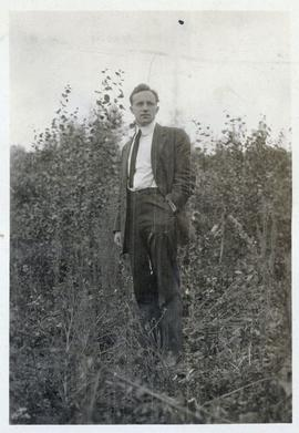 Man in jacket and tie posing in a field