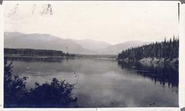 Lake or inlet flanked by trees with mountains in the background