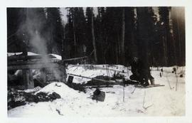 Man on snowshoes crouching in front a fire next to a shack