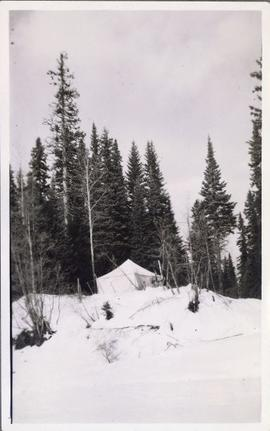A tent perched on a snowy hill top
