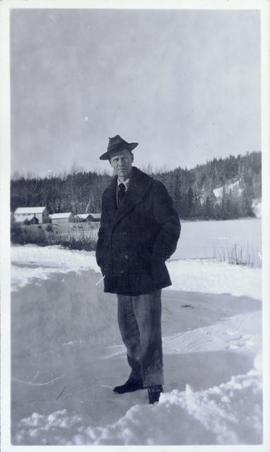 Man in hat and wool jacket standing in the snow