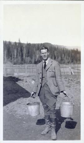 Man with two buckets going to feed the pigs