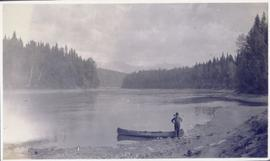 Man standing beside a canoe on the shore