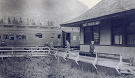 A woman sitting in front of the Prince Rupert train station
