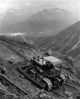 Dozer on Cliff, Cassiar Valley in Background