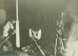 Two unidentified First Nations men making wooden paddles by an evening camp fire
