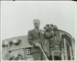 Ray Williston standing on the deck of a train
