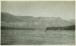 A canoe on a body of water with the mountains in the background