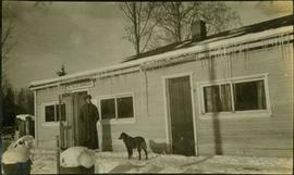 A man and a dog standing in front of the B.C. Police Barracks