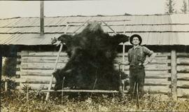 A man standing next to a stretched bear skin