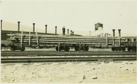 Grand Truck Pacific flatcars loaded with long logs and men posing in front