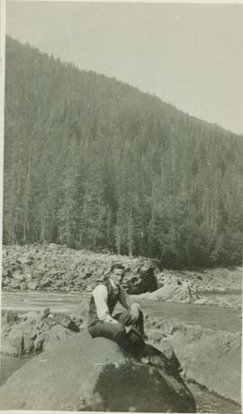 A man sitting on top of a rock next to a river