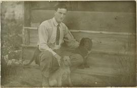 A man sitting on some stairs with two small dogs and a cat