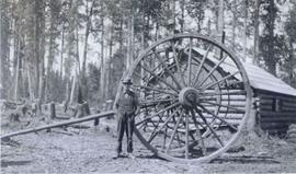 Men posing by large wagon wheels and axle for hauling logs with log cabin behind