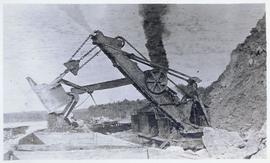 Steam shovel excavating and placing rubble into railcars