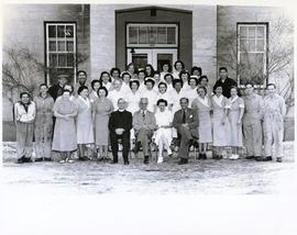 Group photo of hospital workers (?) outside a wooden plank building - possibly a hospital (?)