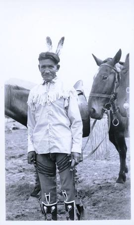 First Nations man holding the reins of a horse