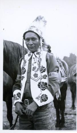 First Nations man wearing feather headdress and embroidered vest and shirt standing holding the r...