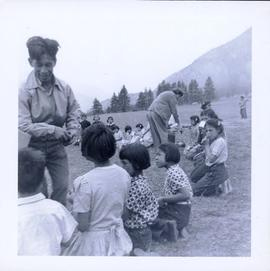 Circle of First Nations children seated on a grassy field receiving food from adults