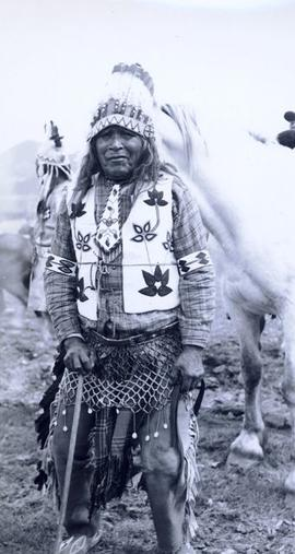 Elderly First Nations man in full regalia with a saddled horse in background