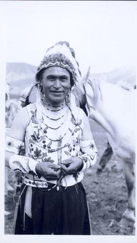 First Nations man in full regalia with saddled horse in background