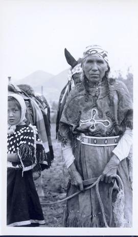 First Nations woman and child in full regalia with saddled horses in background