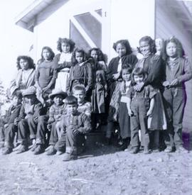 Travel to Anahim Lake, 1952 - Group photo of First Nations children of all ages standing outside a white planked building