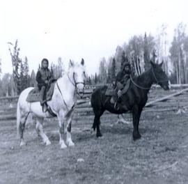 Travel to Anahim Lake, 1952 - Two First Nations children on horses in a fenced field