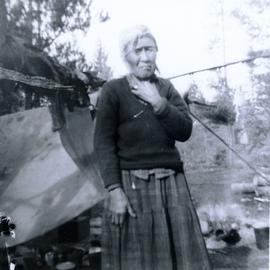 Travel to Anahim Lake, 1952 - Elderly First Nations woman standing in front of a fire and a tent holding her throat