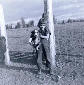 Travel to Anahim Lake, 1952 - Young European girl holding a puppy in front of a barbed wire fence