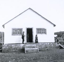 Three First Nations children and one man standing by the doorway of a whitewashed building