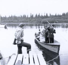 European woman on dock watching boat being pulled to dock by RCMP officer ; supplies, two European men and one First Nations boy on board