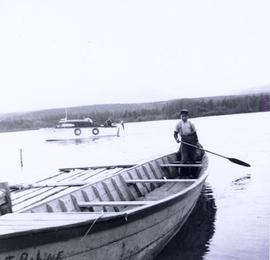 "First Nations boy at back of canoe named ""Fort Babine"" holding a paddle"