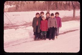 A group of children standing on a snow-covered road