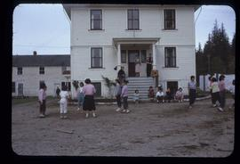 Several First Nations children playing in front of a white-washed school
