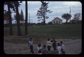 Several children playing on a grassy field with a white house in the distance
