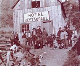 Group portrait of working men and 6 dogs standing outside a Hotel and Restaurant