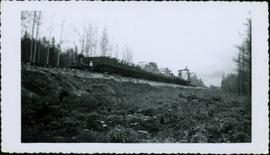 Railroad ties being hauled past Red Rock on a flat bed BCR railcar