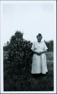 Mrs. John Marcoll Sr. standing in a field next to a lilac bush