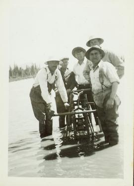 Five men standing in flood water beside a utility car on the CNR tracks