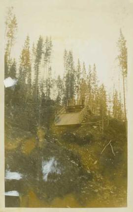 Unidentified man standing at the top of an empty wooden flume (?) situated at the top of a mounta...