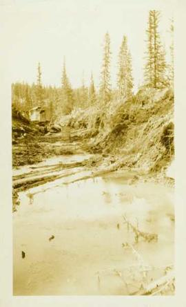 Water filled ditchline with steamshovel visible in background