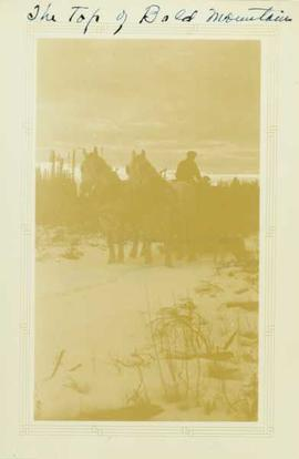 Men and supplies aboard a two horse driven sleigh on top of Bald Mountain in the winter