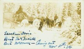 Four men posed within or beside two horse drawn carriages in a winter landscape