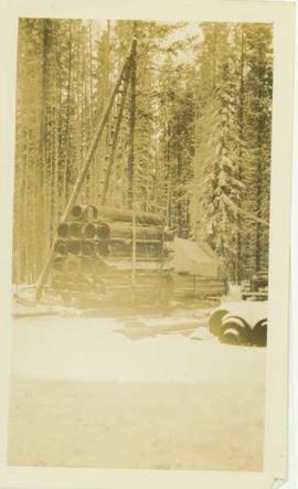 Large sled carrying freight into a mining (?) camp in winter
