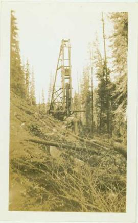 Unidentified man standing on a hillside, a pile driver is visible in the background
