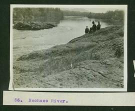 Three men sitting on the rocky banks of the Nechako River
