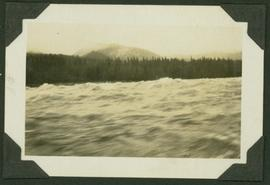 Water view of the Ne Parle Pas Rapids, Peace River; treed shoreline and mountain visible in backg...